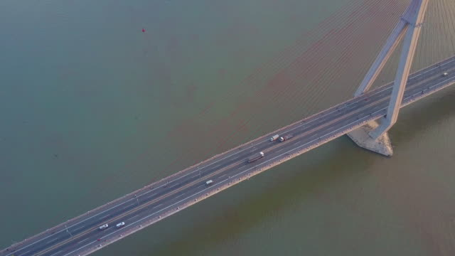 DRONE: Flying above a busy bridge crossing the murky river in sunny Vietnam. DRONE: Flying above a busy concrete suspension bridge crossing the murky river in sunny Vietnam. Countless vehicles drive up and down the freeway and cross the large murky river. Amazing architecture suspension bridge stock videos & royalty-free footage