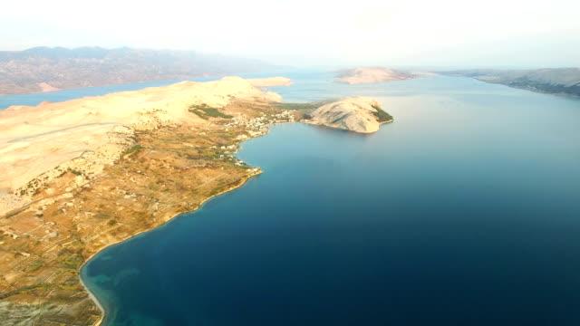 Flying above barren coast of Pag island a sunset, Croatia