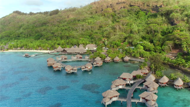 AERIAL: Flying above beautiful luxurious deluxe overwater villas and beachfront bungalows facing the turquoise lagoon in lush tropical island resort on a beautiful sunny day on summer vacation video