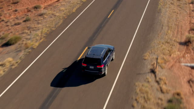 AERIAL CLOSE UP Flying above black SUV car driving on empty road in sandy desert
