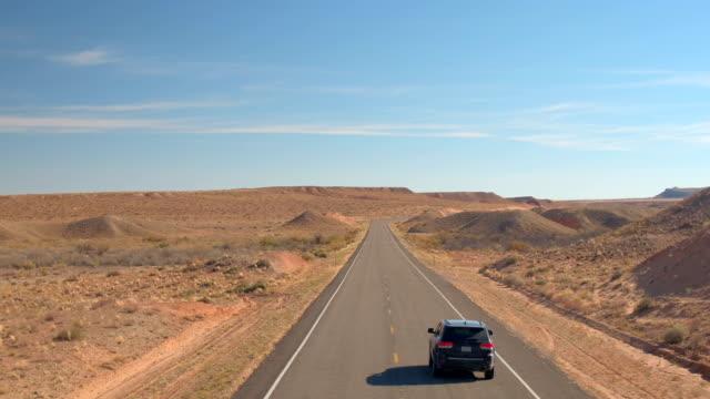 vídeos de stock, filmes e b-roll de aérea: voando acima carro suv preto dirigindo na estrada vazia através do deserto de areia - veículo terrestre