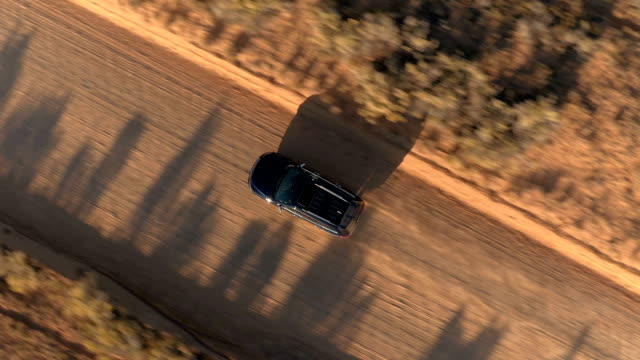 AERIAL CLOSE UP: Flying above black SUV car traveling along dusty desert road AERIAL: Black SUV car driving along the empty dusty road trough dry meadow desert valley in Utah on sunny morning. Flying above jeep traveling on straight dirt route into Capitol Reef at golden sunset country road stock videos & royalty-free footage