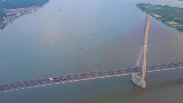 AERIAL: Flying above bridge crossing the large murky river on a sunny evening. AERIAL: Flying high above a suspension bridge crossing the large murky river on a sunny evening. Spectacular shot of traffic going up and down the freeway bridge connecting Vietnamese town and nature. suspension bridge stock videos & royalty-free footage