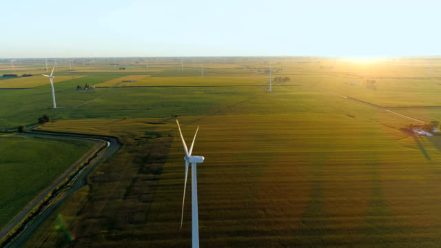 Flying above countryside field and wind farm into sunset