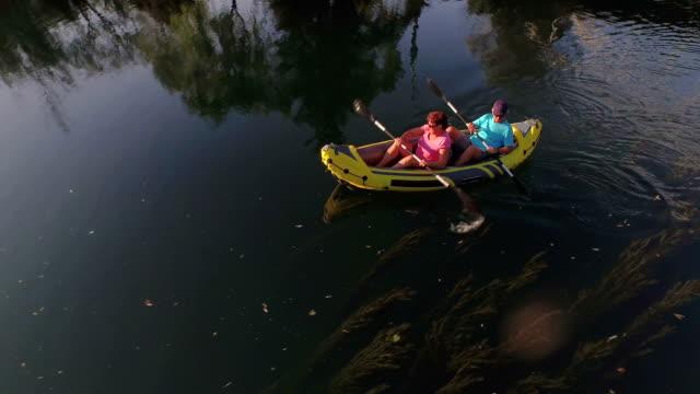 VUE AÉRIENNE : Voler au-dessus de l'heureux couple profitant de vacances du kayak sur le fleuve en soirée d'été - Vidéo