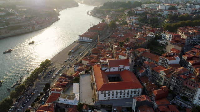 Flying above historic centre of Porto at sunset High top view dron flying above ancient city. Historic centre, buildings with red tiled roof on embankment and water of Douro river in the sunlight. Porto, Portugal portugal stock videos & royalty-free footage