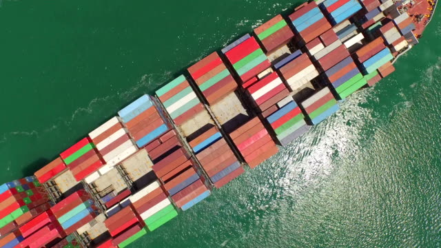 AERIAL: Flying above huge container ship fully loaded with freight cargo, freight transportation video