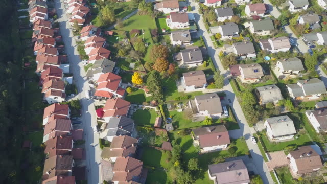 AERIAL: Flying above idyllic suburban town with row houses and green gardens video