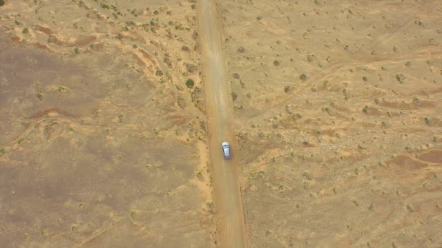 AERIAL: Flying above the car driving through huge sandy desert video