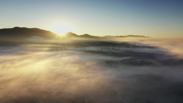 Flying above the clouds and Mountain in sunrise time