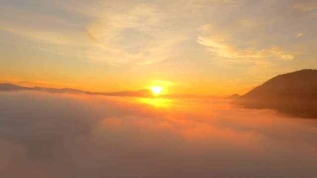 AERIAL: Flying above the clouds at amazing golden sunset AERIAL: Flying above the clouds at amazing golden sunset. Sun rising over the clouds horizon over land stock videos & royalty-free footage