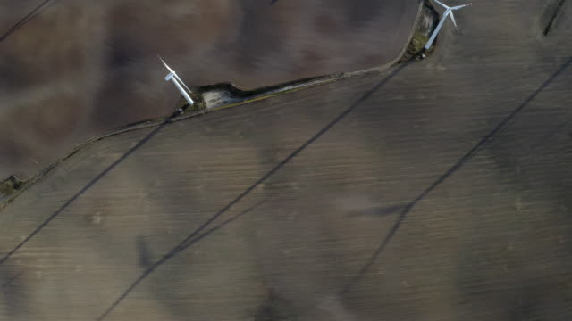 Flying Above Wind Turbines In A Wind Farm For Energy Production Generating Environmentally Friendly Energy On Open Grass Field