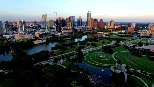 Flying Across Butler Park near Downtown Austin Texas with Skyline Cityscape and entire Texas Hill Country View Flying Across Butler Park near Downtown Austin Texas with Skyline Cityscape and entire Texas Hill Country View with Austonian and Frost Bank tower in View post modern architecture stock videos & royalty-free footage