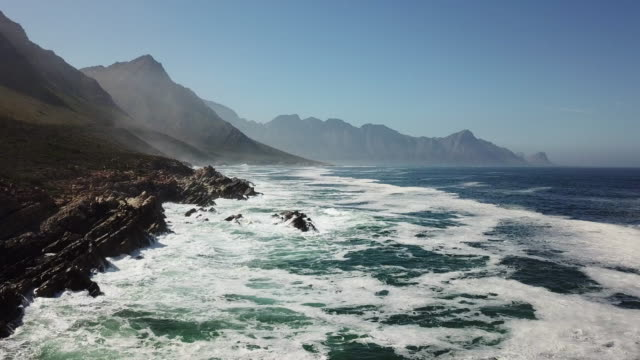 Flying along a beautiful coastline Aerial view over the waves crashing against a rocky shoreline - South Africa south africa stock videos & royalty-free footage