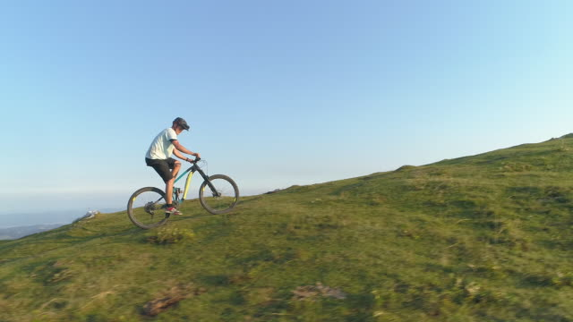 DRONE: Flying along an athletic man pedalling an e-bike up a steep grassy hill.