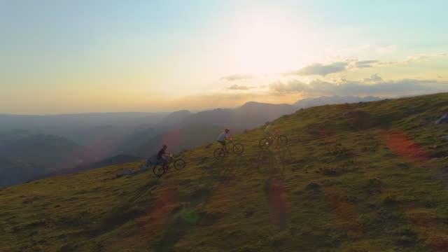güneş parlamasi: bir tepeye bisikletle çıkan üç aktif turist boyunca uçuyorlar. - turizm stok videoları ve detay görüntü çekimi