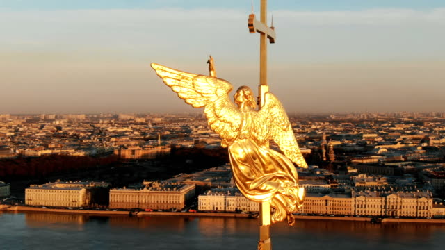 Flying around an angel on spire of Peter and Paul Fortress at sunset, close-up. Panorama of historical center of St. Petersburg