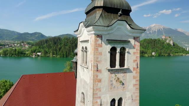 空から見たクローズアップ:フライングにブレッド教会タワーの島の真ん中の、美しい湖 - スロベニア点の映像素材/bロール