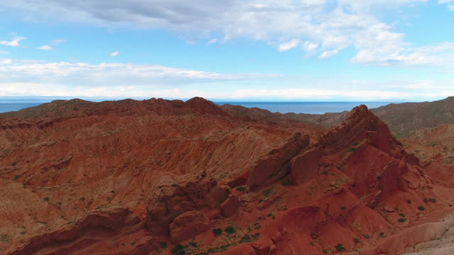 Flying around red canyon rock. Martian landscape. Lake and blue sky. Aerial view. video