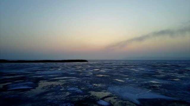 fliegen bei sonnenaufgang bei einbruch der dämmerung im winter, bedeckt mit schnee und eis - schneeflocke sonnenaufgang stock-videos und b-roll-filmmaterial