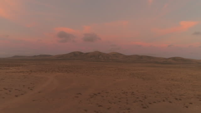 AERIAL: Flying away from big volcanic structure in pink colored desert sunset. video