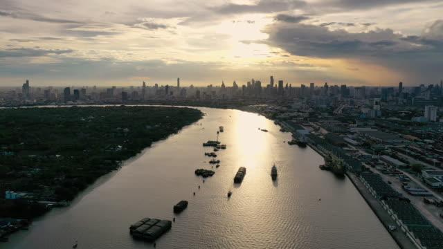 flying backward aerial bangkok cityscape chao phraya river in sunset - элемент здания стоковые видео и кадры b-roll