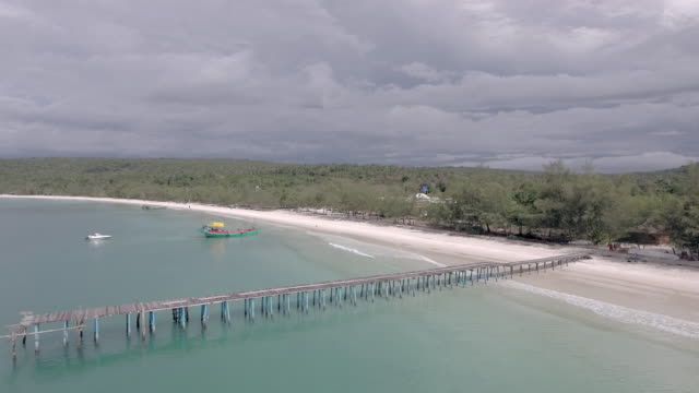 flying backwards over the wooden pier on a white beach and speedboats moored around it Aerial drone shot: flying backwards over the wooden pier on a white beach and speedboats moored around it under dark cloudy skies back to back stock videos & royalty-free footage