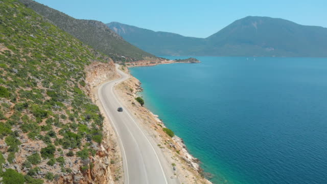 DRONE: Flying behind a car exploring the island by driving down a coastal road. DRONE: Flying behind a tourist car exploring the remote island in the Mediterranean by driving down a scenic coastal road. Tourists cruising along the breathtaking shoreline of Lefkada in a grey car. greek islands stock videos & royalty-free footage