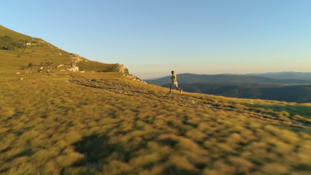 AERIAL: Flying behind an energetic man running up a grassy hill on sunny evening