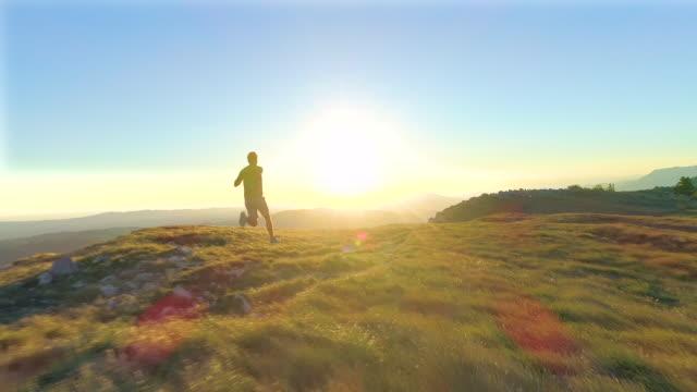 antenn: flygande bakom atletisk ung man tävlar ner en gräsbevuxen kulle vid solnedgången. - jogging hill bildbanksvideor och videomaterial från bakom kulisserna