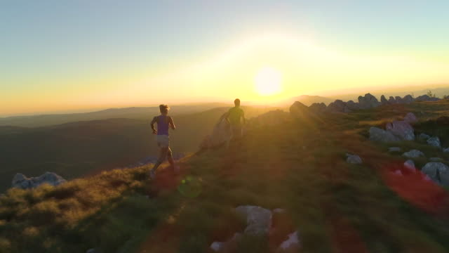 DRONE Flying behind sporty tourist couple running along mountain trail at sunset
