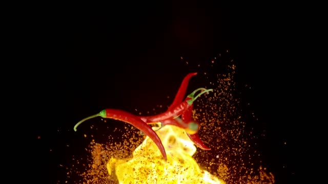 flying burning chili peppers and spices. high speed, phantom flex 4k - chilli con carne video stock e b–roll
