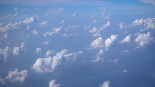 fliegen durch flauschige weiße wolken unten am blauen himmel. - zirrus stock-videos und b-roll-filmmaterial