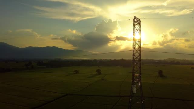 日没で背の高い電圧の電気タワー下で飛ぶ - 稲点の映像素材/bロール
