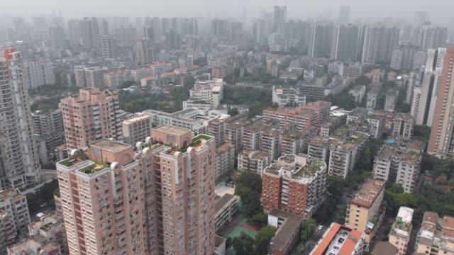 複数階建ての住宅の屋根の上にドローンを飛ばします。 - 中国 広州市点の映像素材/bロール