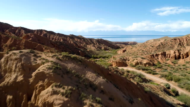 flygande snabbt över red canyon och vägen på solig dag. flygfoto - kulle bildbanksvideor och videomaterial från bakom kulisserna