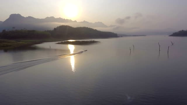 Flying follow a fisherman boat with beautiful reflection of sunlight in lake with drone, Aerial shot