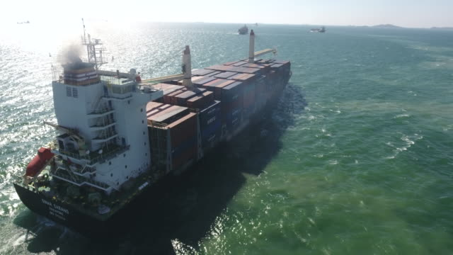flying follow big container ship in ocean, aerial video - nave cisterna video stock e b–roll