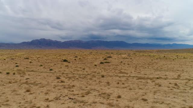 fliegen nach vorn über beige trockener sandwüste. bewölkten himmel und berge im hintergrund. luftaufnahme. - niedrig stock-videos und b-roll-filmmaterial
