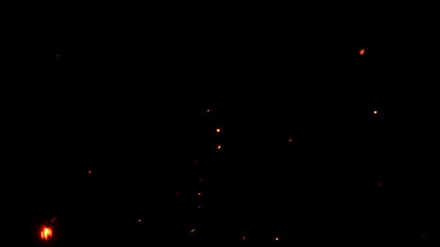parlayan yangın uçan bir siyah arka plan ile kıvılcım - kıvılcım stok videoları ve detay görüntü çekimi