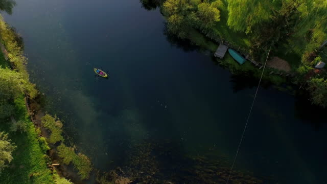 AERIAL: Flying high above man and woman kayaking on beautiful river in sunny summer video