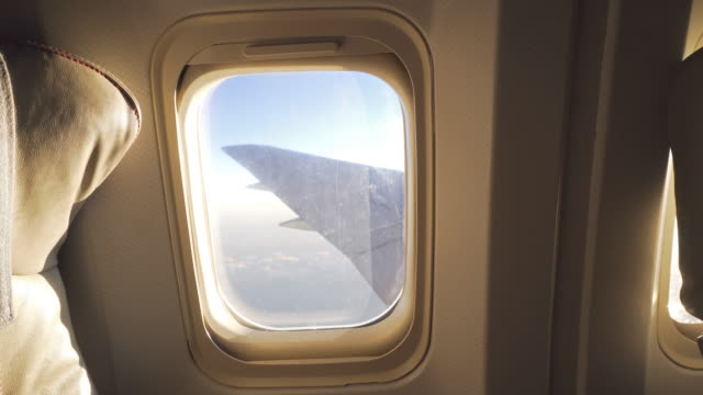 Flying high up in sky, looking out through airplanes window video