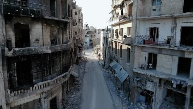 flying in a street of aleppo with a drone. ravaged buildings without any windows, and burned houses. - wojna filmów i materiałów b-roll