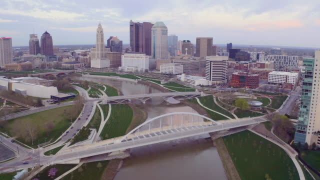 flying in over the columbus ohio skyline featuring scioto river - элемент здания стоковые видео и кадры b-roll