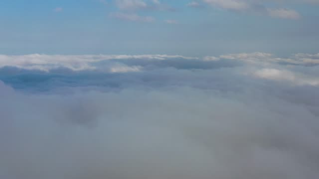 Flying in the midst of a dreamy cloudscape over mountains.