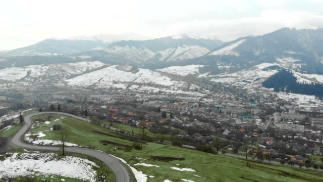 Flying in the mountains in winter in cloudy weather. City in the mountains and green grass
