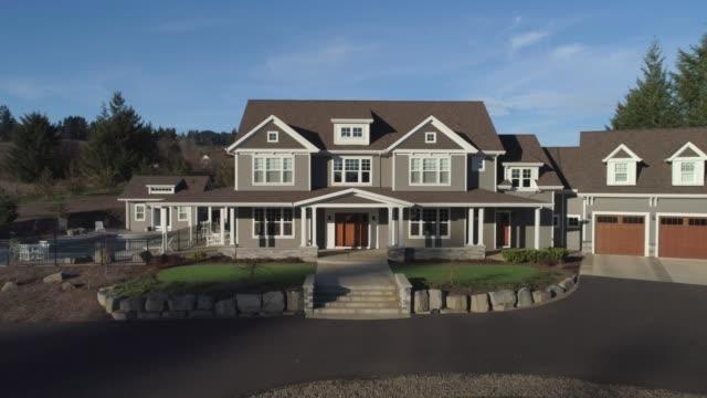 vídeos de stock e filmes b-roll de flying into front porch of new custom home - driveway, no people