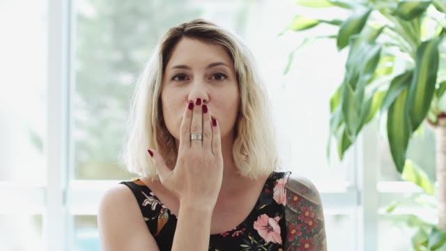 flygande kyss av vacker ung blond kvinna, porträtt, inomhus - blåsa en kyss bildbanksvideor och videomaterial från bakom kulisserna