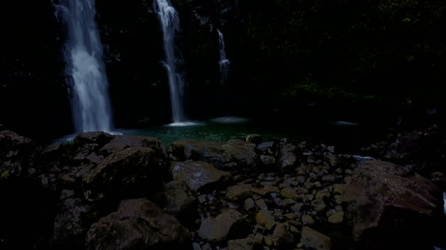 Flying Low Above Rocks Around Pool of Water from Waterfall