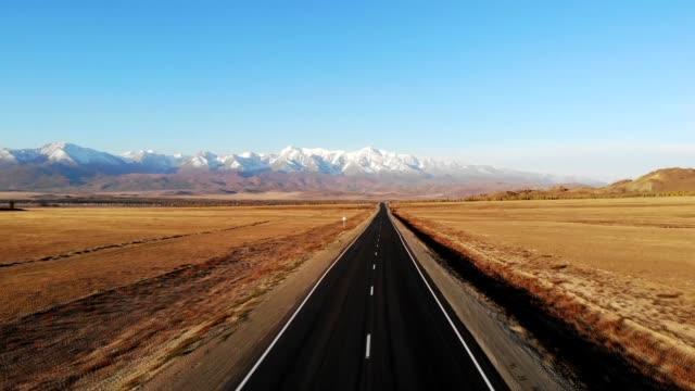 fliegen auf einem quadrocopter über eine autobahnstraße, vor dem hintergrund der berge im herbst an einem klaren tag, altai - hochplateau stock-videos und b-roll-filmmaterial